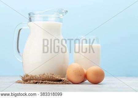 Milk in glass and jug and eggs in front of blue background with copy space