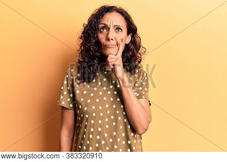 Middle age beautiful woman wearing casual t shirt thinking concentrated about doubt with finger on chin and looking up wondering