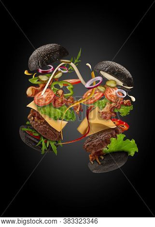 Two Palatable Black Burgers With Flying Ingredients On Black Background. Ham, Beef Cutlet, Cheese, S