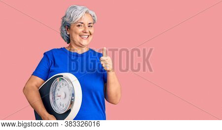 Senior woman with gray hair holding weight machine to balance weight loss smiling happy and positive, thumb up doing excellent and approval sign