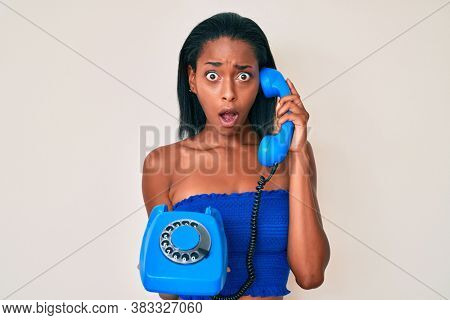 Young african american woman holding vintage telephone in shock face, looking skeptical and sarcastic, surprised with open mouth