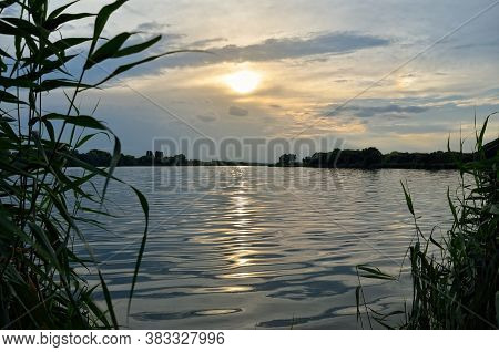 Sunbeams At Sunset Are Reflected In The Lake