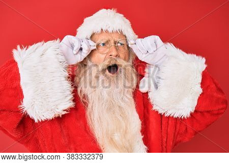 Old senior man with grey hair and long beard wearing santa claus costume holding glasses angry and mad screaming frustrated and furious, shouting with anger. rage and aggressive concept.