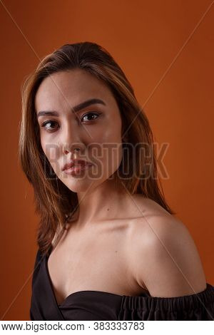 Charming Elegant Fashion Model Wearing Black Dress With Deep Neckline Posing On Orange Background. A