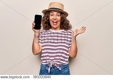 Middle age beautiful woman wearing summer hat holding smartphone showing screen celebrating achievement with happy smile and winner expression with raised hand