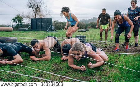 Group Of Participants In An Obstacle Course Crawling Under Electrified Cables