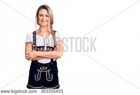 Young beautiful blonde woman wearing oktoberfest dress happy face smiling with crossed arms looking at the camera. positive person.