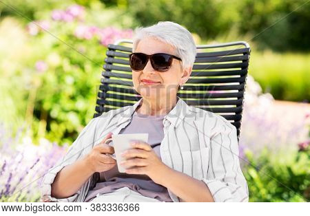 old age, retirement and people concept - close up of happy senior woman drinking coffee or tea at summer garden