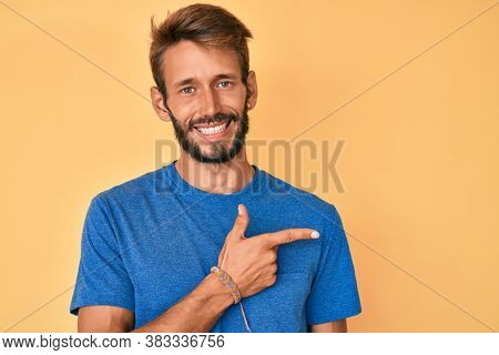 Handsome caucasian man with beard wearing casual clothes cheerful with a smile of face pointing with hand and finger up to the side with happy and natural expression on face