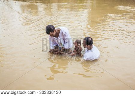 QASR El-YAHUD, ISRAEL - MARCH 2, 2020: The place of baptism of Jesus Christ on Jordan River. Baby Baptism Ceremony. Two men in white shirts stand in the water and hold babies.  concept of pilgrimage