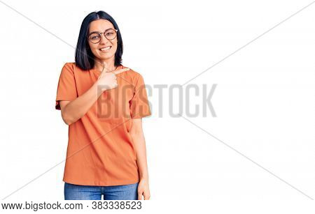 Young beautiful latin woman wearing casual clothes cheerful with a smile of face pointing with hand and finger up to the side with happy and natural expression on face