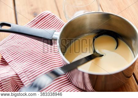 christmas and seasonal drinks concept - pot with eggnog and ladle with kitchen towel on wooden background