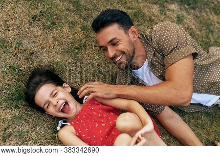 Top View Of A Cheerful Father Playing With His Daughter On The Grass Outdoors. Dad Enjoying At Day O
