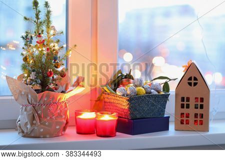 Christmas tree, Christmas decorations, candles, garland  and Christmas gifts on a window sill. Christmas eve concept