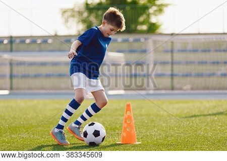 Boy In Soccer Uniform Practice With Ball. Child Kicking Ball On Grass Stadium. Young Athlete Improvi