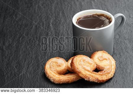Flaky  Pastry Hearts Glazed With Caramelized Sugar And Cup Of Coffee On Black Stone Background