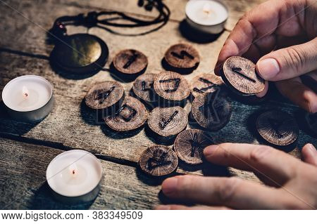 Hand Holding Wooden Runes, Esoteric And Spirituality, Reading And Fortuneteller, Details With Candle