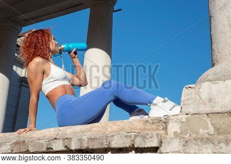 Young Red-haired Sportswoman Woman Drinks Water From A Bottle, On The Outdoor. In Sports Leggings, H