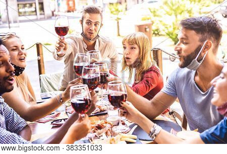Friends Toasting Red Wine At Restaurant Bar With Face Masks - New Normal Friendship Concept With Hap