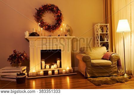 Fireplace, Chair And Floor Decorated Autumn Wreath. Night Windows At The Background. Autumn Interior