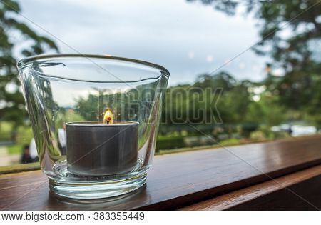 Tea Light Candle Sitting Inside A Small Glass Jar Placed On A Window Sill, Overlooking A Tranquil Ga