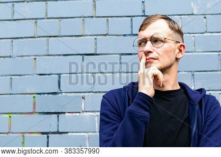 Portrait Of Young Goodlooking Man Against Grey Brickwall. Lots Of Copyspace.