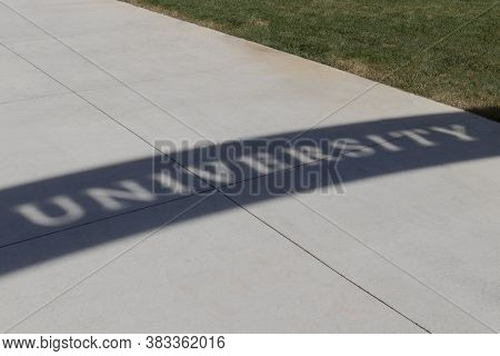 University Text In Shadow On The Ground Of A College Campus.