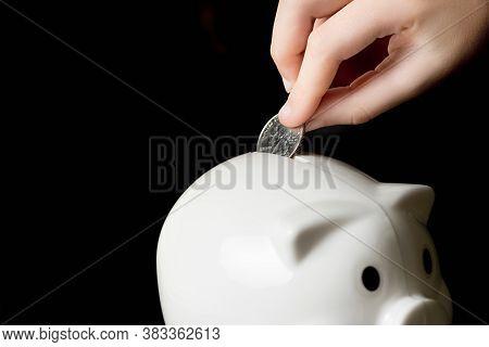 Child's Hand Putting A Quarter Into A Piggy Bank.  Saving Money Concept, Black Background