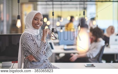 beautiful modern african Muslim businesswoman in office, wearing hijab at creative modern startup coworking space