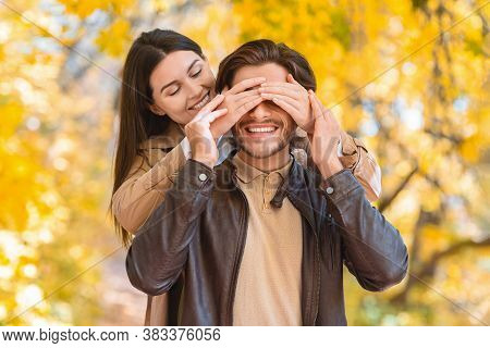 Woman Closing Eyes Of Her Boyfriend, Dating In Autumn Park, Enjoying Time Together