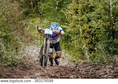 Cyclist Athlete With Mountain Bike Walking Uphill On Forest Trail