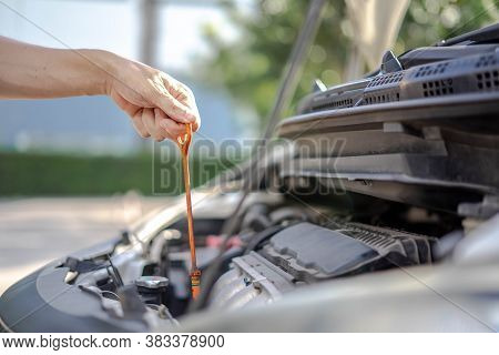 Man Checking The Oil Level In Car Engine, Check And Maintenance The Oil Level In Car With Yourself.
