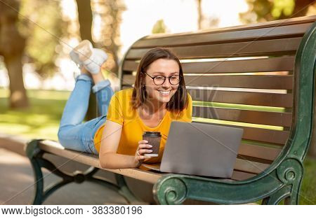 Cheerful Student Girl Using Laptop Computer Browsing Internet Lying On Bench In Park Outside. Online