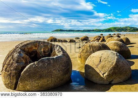 The large spherical boulders Moeraki and their remains on sandy beach. The popular tourist attraction. New Zealand. Low tide in the Pacific ocean. The concept of exotic and ecological tourism
