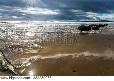 The Pacific ocean tide begins. New Zealand. Moeraki's huge round boulders on a sandy beach. The sun's rays are reflected in the ocean water. Noon. The concept of ecological, photo and exotic tourism