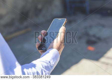 Man Uses His Mobile Phone Outdoor, Close Up. Image Of A Mans Hands Using A Mobile Smart Phone