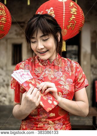 Happy Asian Woman In Traditional Chinese Dress Holding A Red Pocket With Chinese One Hundred Yuan Ba