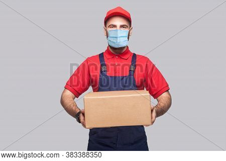 Delivery On Quarantine. Portrait Of Young Man With Surgical Medical Mask In Blue Uniform And Red T-s
