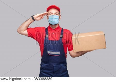 Delivery On Quarantine. Give Salute Or Yes Sir! Young Man With Surgical Medical Mask In Blue Uniform