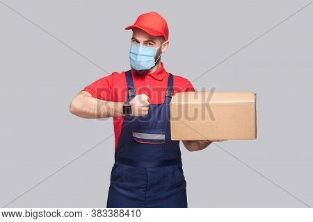 Delivery On Quarantine. Ontime Service! Man With Surgical Medical Mask In Blue Uniform And Red T-shi