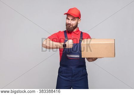 Ontime Delivery Service! Young Logistic Man With Beard In Blue Uniform And Red T-shirt Standing, Hol