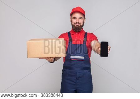 This Is For You! Young Smiling Logistic Man With Beard In Blue Uniform And Red T-shirt Standing, Hol