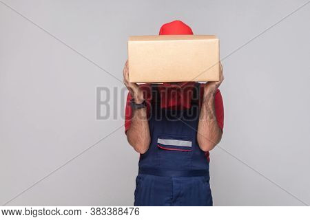 Portrait Of Young Logistic Delivery Man With Beard In Blue Uniform And Red T-shirt Standing And Cove