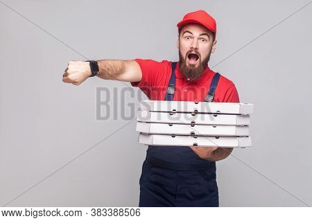 Hurry Up! Time Is Gone. Young Amazed Delivery Man With Beard In Blue Uniform And Red T-shirt, Holdin