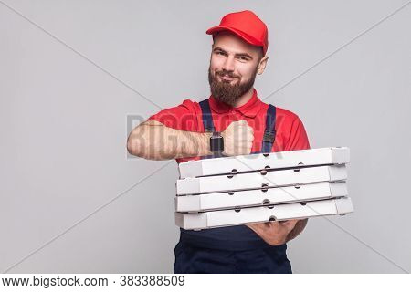 In Time! Young Cheerful Delivery Man With Beard In Blue Uniform And Red T-shirt Standing,holding Sta