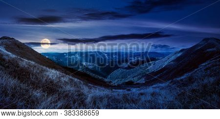 Mountain Landscape In Autumn At Night. Dry Colorful Grass On The Hills. Ridge Behind The Distant Val