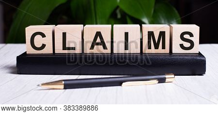 The Word Claim Is Written On The Wooden Cubes That Sit On The Diary Near The Pen. Legal Concept