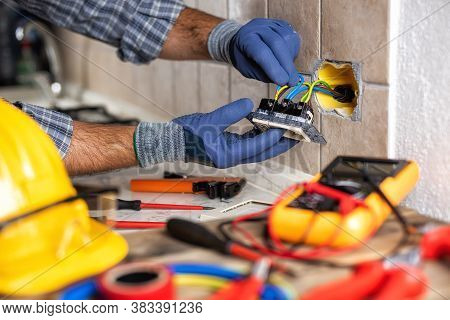 Electrician At Work With Safety Equipment On A Residential Electrical System. Electricity.