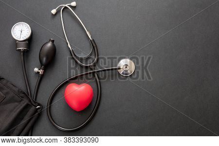 Medical Stethoscope And Sphygmomanometer On Black Background, Top View.