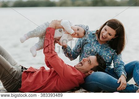 Happy Young Family Sitting Near The Water. Mom, Dad And Their Little Baby Daughter Sitting Together.